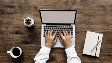 Bilde: En person skriver på en mac. Ved siden av står en kaffekopp og en notisbok.