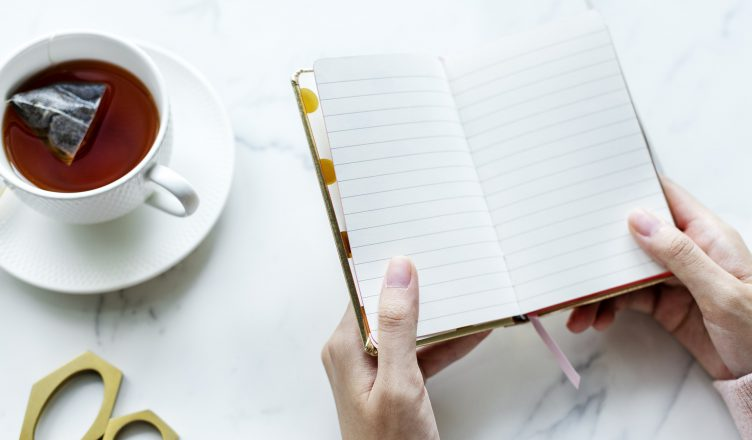 Image: A person is holdning a notepad. A cup of tea and scissors are on the table beneath.