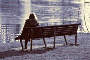 Bilde: En person sitter alene på en benk ved vannet