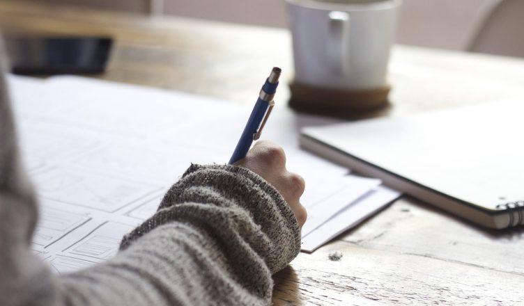 Bilde: Kvinne skriver i en notisbok. En kaffekopp står på bordet.